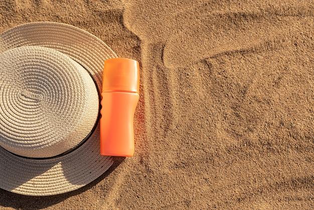 日焼け止めやローション用のオレンジ色のボトル。砂の上に黒い影のあるコンテナ。夏の帽子。休暇中の夏。