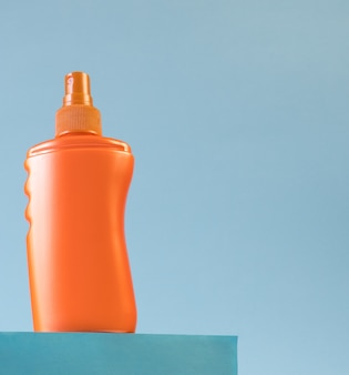 Оранжевая бутылка солнцезащитного крема на подиуме на голубом фоне