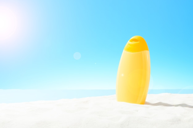 Orange bottle of sunscreen on a sandy beach