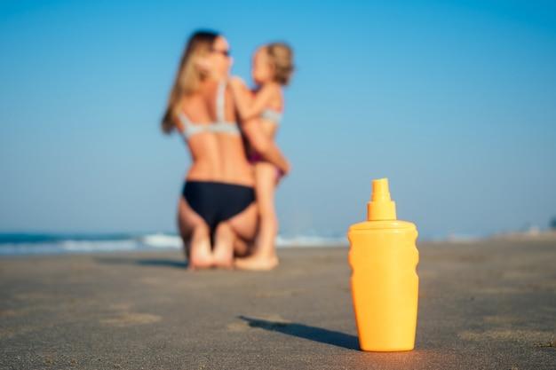 어머니와 딸 옆 해변에서 자외선 차단제와 함께 오렌지 병.