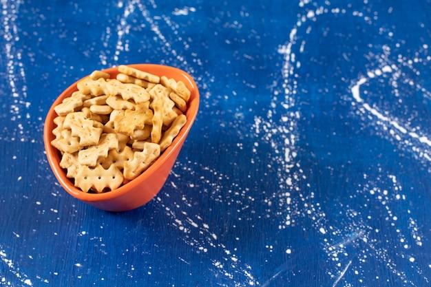 Ciotola arancione di piccoli cracker salati sulla superficie di marmo
