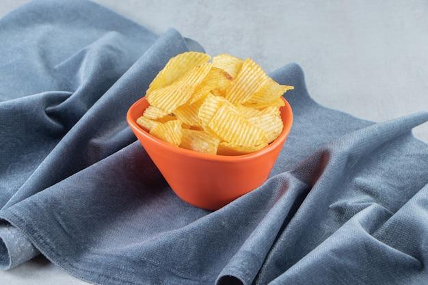 Orange bowl of tasty ripple chips on stone.