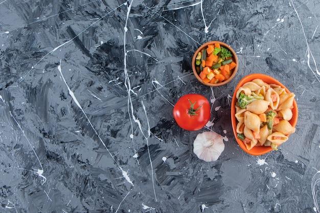 Ciotola arancione di gustosa pasta di conchiglie con insalata di verdure su superficie di marmo.