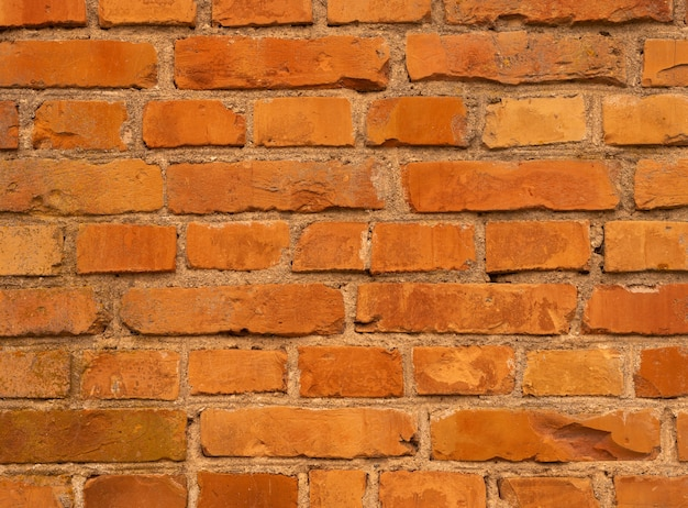 オレンジ色のレンガの壁。ブリックウォールの背景、古いヴィンテージの質感。