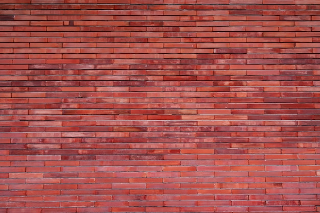 オレンジ色のレンガの壁のテクスチャ背景。ビンテージパターンの壁紙。空のレンガの壁。オレンジシェードブリックウォール背景。家の壁のインテリアデザイン。家のオレンジ色の壁。