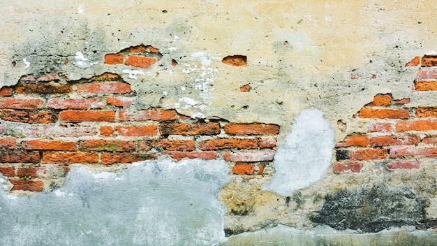 손상된 석고와 주황색 벽돌 벽