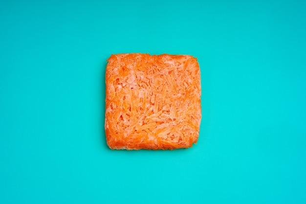 冷凍すりおろしたにんじんのオレンジ色のレンガ。冷凍食品の調達。半完成。