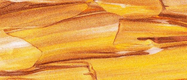 Оранжево-коричневый фон с блестящими мазками. абстрактная текстура краски. креативные мазки золотой краской. концепция макияжа. праздничный фон