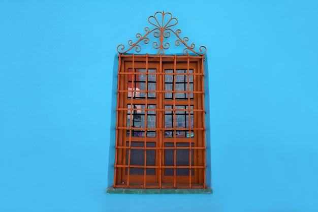 Orange brown decorative wrought iron windowon blue concrete wall