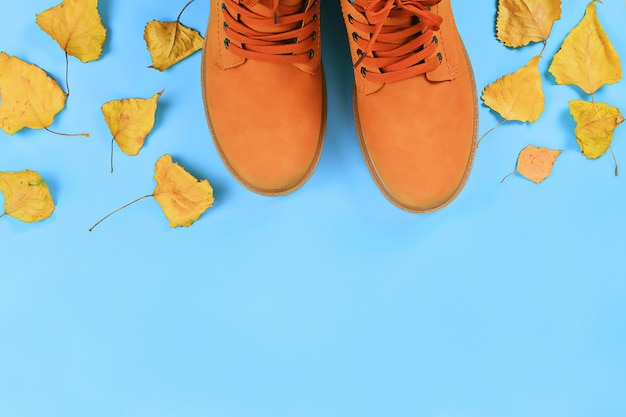 Orange brown mens autumn boots on blue pastel background. top view, copy space.
