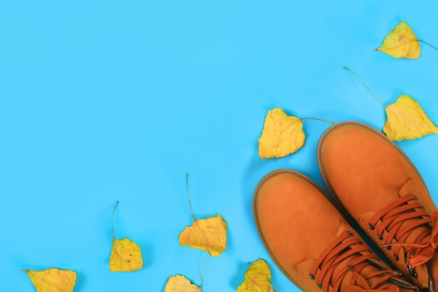Orange brown mens autumn boots on a blue pastel background. top view, copy space.