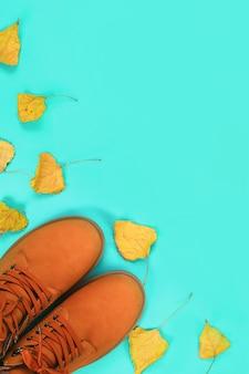 Orange brown mens autumn boots on mint pastel . top view, copyspace.