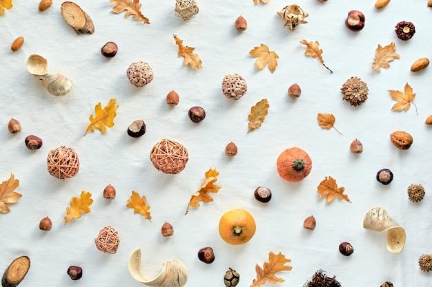 オレンジ、茶色の白い秋の背景。カボチャ、ドングリ、ナッツ、秋の紅葉と編み玉の抽象的な幾何学的な斜めパターン。白い繊維の平面図です。