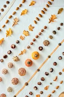 オレンジ、茶色の白い秋の背景。白い繊維の平面図です。カボチャ、ドングリ、ナッツ、秋の紅葉と編み玉の抽象的な幾何学的な斜めパターン。