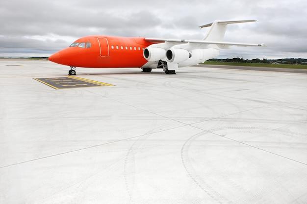 An orange business jet on the apron