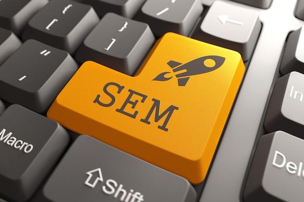 Orange button with sem on black computer keyboard. marketing concept.