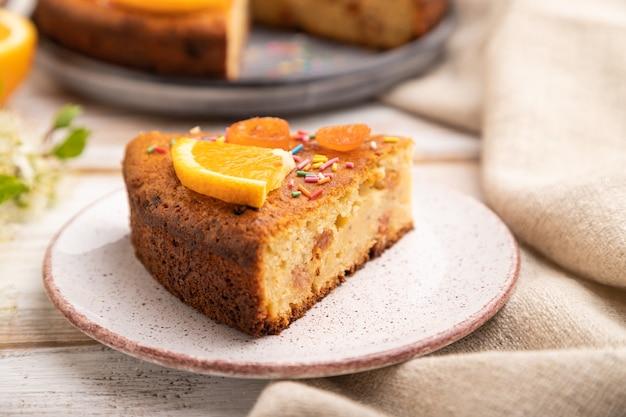 オレンジ色のケーキと白い木製の背景とリネンのテキスタイルのコーヒーのカップ。