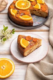 オレンジケーキと白い木製のテーブルとリネンの繊維にコーヒーのカップ。側面図、クローズアップ。