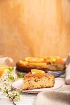 オレンジケーキと白い木製のテーブルとリネンの繊維にコーヒーのカップ。側面図、コピースペース。