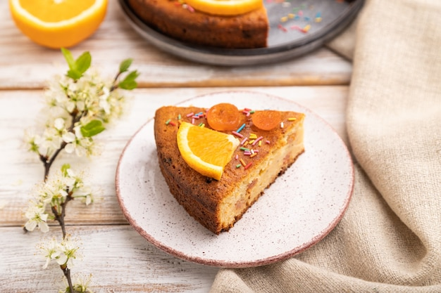 白い木製のオレンジ色のケーキと一杯のコーヒー