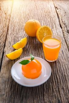 オレンジケーキ、フレッシュオレンジジュースのフルーツ、半分オレンジフルーツ、木製テーブル