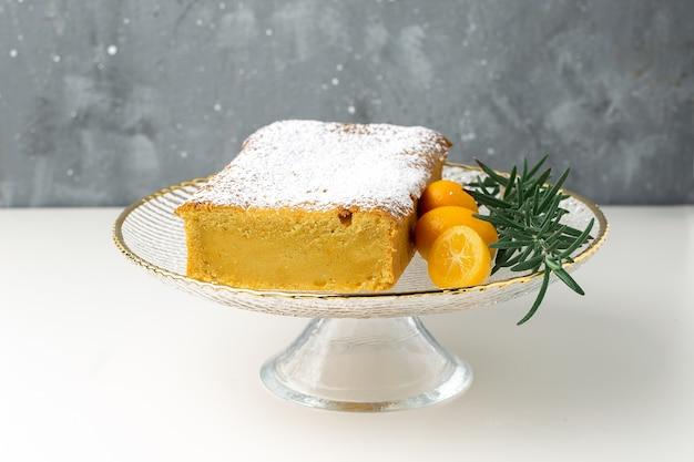 Orange cake on cake stand with kumquats