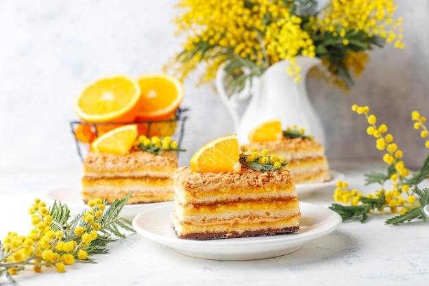 신선한 오렌지 조각과 빛에 미모사 꽃으로 장식 된 오렌지 케이크