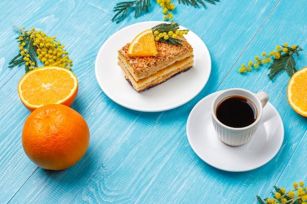 光の新鮮なオレンジスライスとミモザの花で飾られたオレンジケーキ