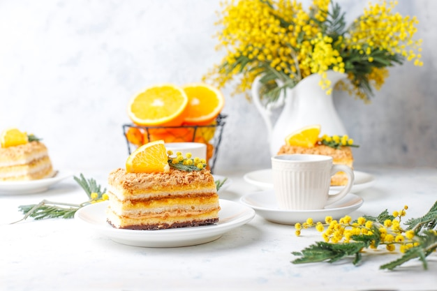 Orange cake decorated with fresh orange slices and mimosa flowers on light