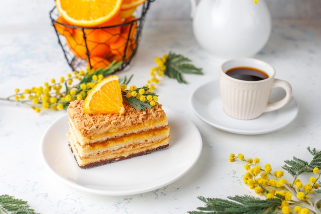 Torta arancione decorata con fette d'arancia fresche e fiori di mimosa sulla luce
