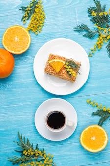 Orange cake decorated with fresh orange slices and mimosa flowers on light