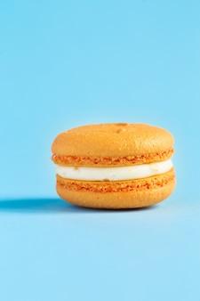 Апельсиновый торт macaron или миндальное печенье на синей стене. разноцветное миндальное печенье. французский макарун