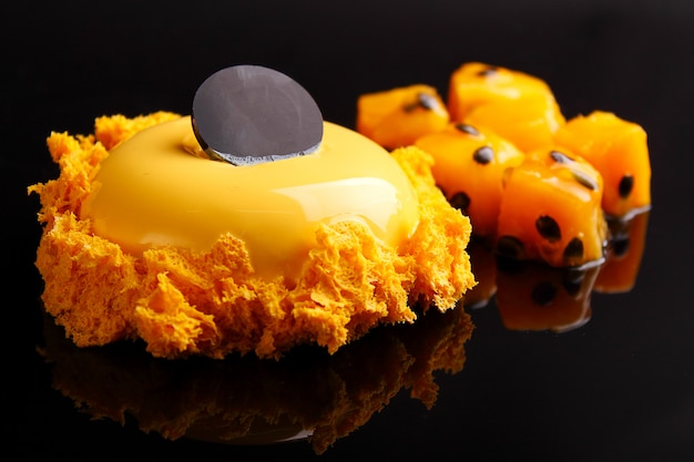 Orange cake in the mirror with passion fruit glaze is decorated with molecular biscuit on a black background.