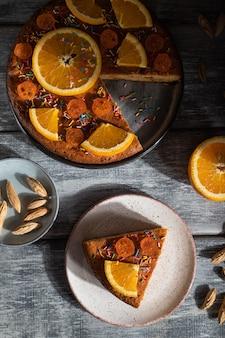 灰色の木製の背景にオレンジ色のケーキ。ハードライト。コントラスト、ローキー。上面図、フラットレイ、クローズアップ。