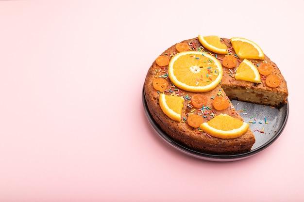 Апельсиновый торт на пастельно-розовом фоне. вид сверху, плоская планировка, копия пространства.