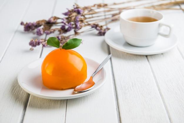 白い木製のテーブルにオレンジ色のケーキ