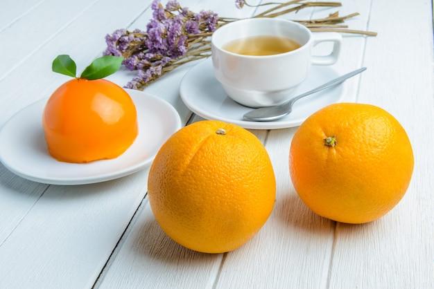 白い木製のテーブルの上のオレンジケーキ
