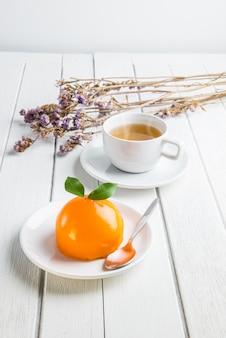 Orange cake on white wooden table