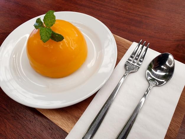 테이블에 나무 접시에 숟가락과 포크와 오렌지 케이크