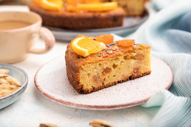 白いコンクリートの背景と青いリネンのテキスタイルにアーモンドとコーヒーのオレンジ色のケーキ。