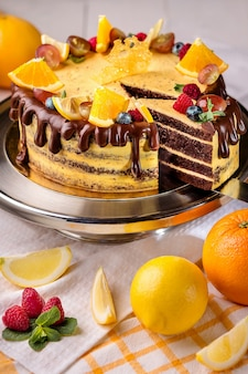 Orange cake with chocolate and orange slices on a platter in a bakery
