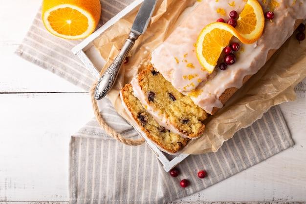 白い素朴な木製の背景にクランベリーと砂糖のアイシングとオレンジ色のケーキ。上面図。閉じる。