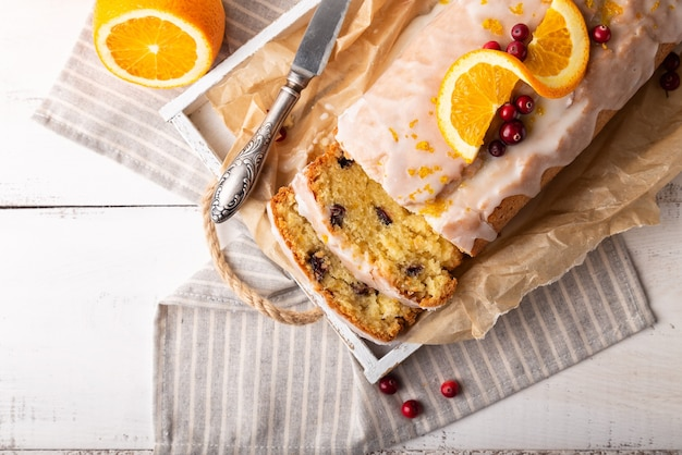 Orange cake with cranberries and sugar icing on white rustic wooden background. top view. close-up.