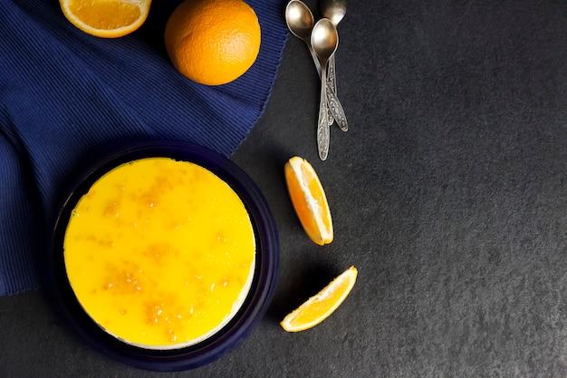 어두운 배경에 크림 무스와 오렌지 젤리가 있는 오렌지 케이크. 평평한 평지, 평면도.