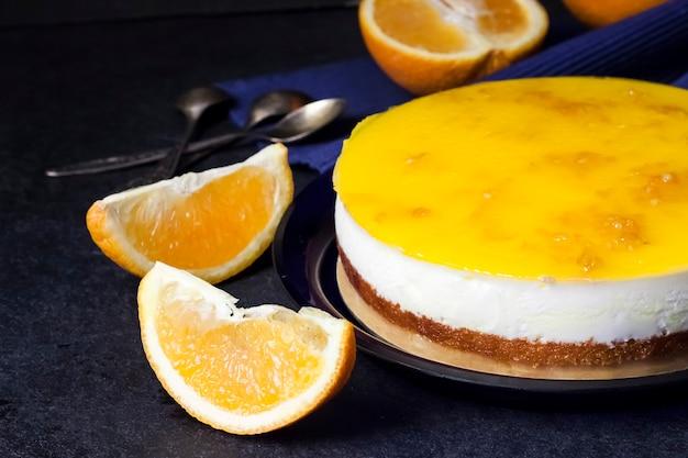 Апельсиновый торт со сливочным муссом и апельсиновым желе на темном фоне