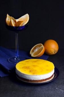 어두운 배경에 크림 무스와 오렌지 젤리를 넣은 오렌지 케이크