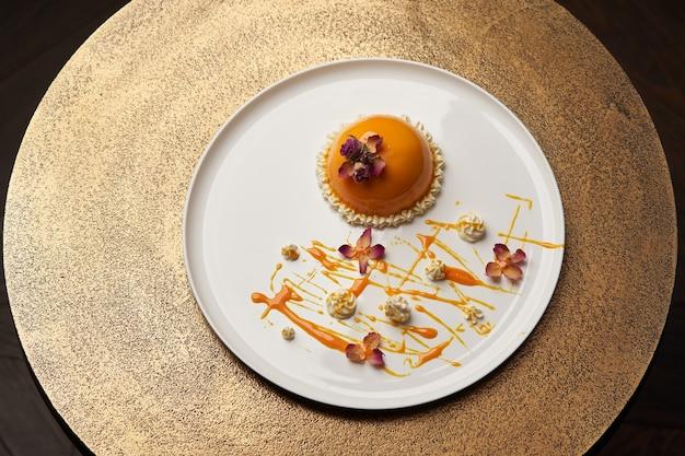 하얀 접시에 크림과 함께 오렌지 케이크입니다. 바나나 무스 케이크, 고급 레스토랑 디저트