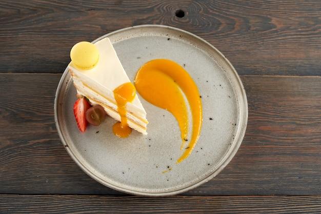 Orange cake with fruit puree macaroon and berries