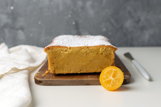 Orange cake with kumquats on wooden cutting board