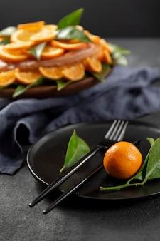 葉とカトラリーとオレンジ色のケーキ
